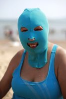 A woman, wearing a nylon mask, smiles as she rests on the shore during her visit to a beach in Qingdao